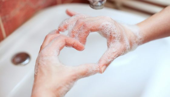 Soapy hand making heart shape