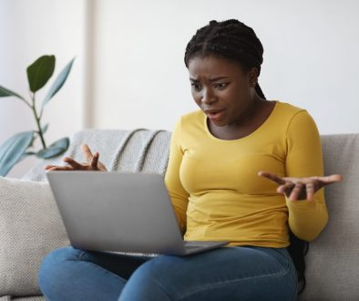 Computer Problems. Confused african american woman having troubles with laptop at home